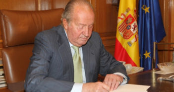 King Juan Carlos signs a document confirming his decision to abdicate the Spanish throne